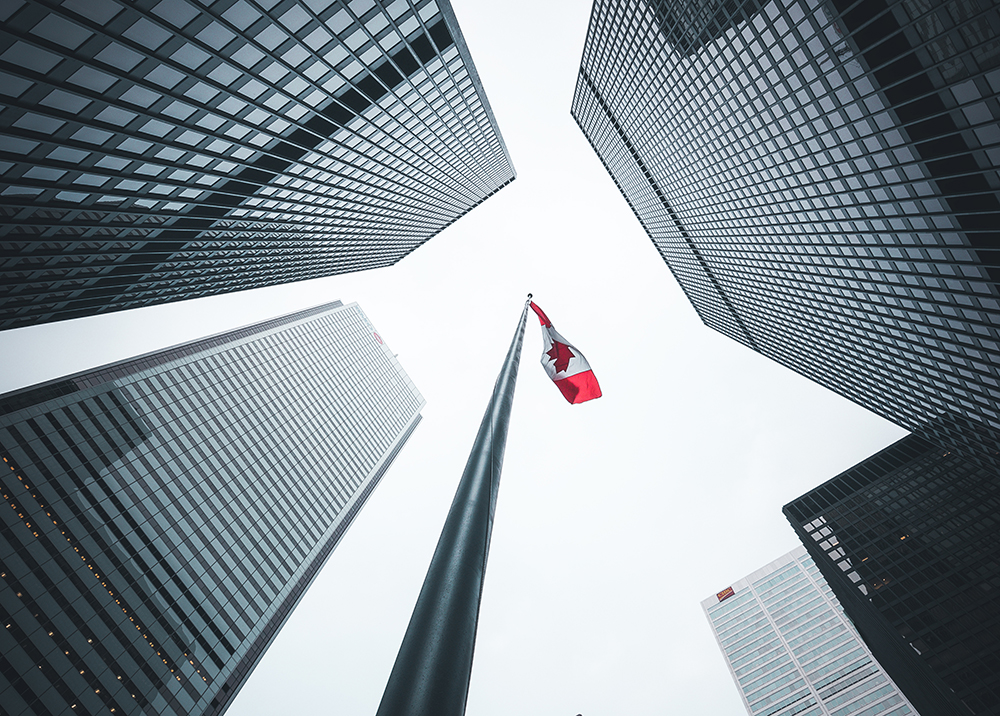 Canadian flag surrounded by skyscrapers