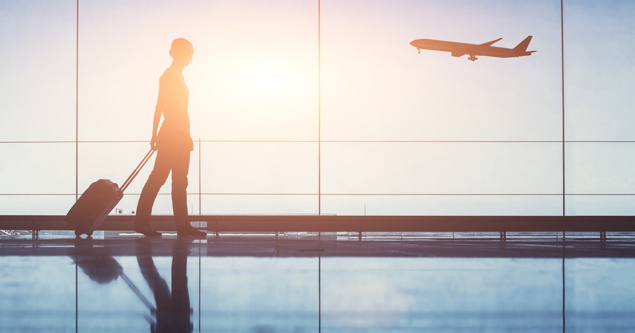 woman with suitcase at airport with plane taking off outside window