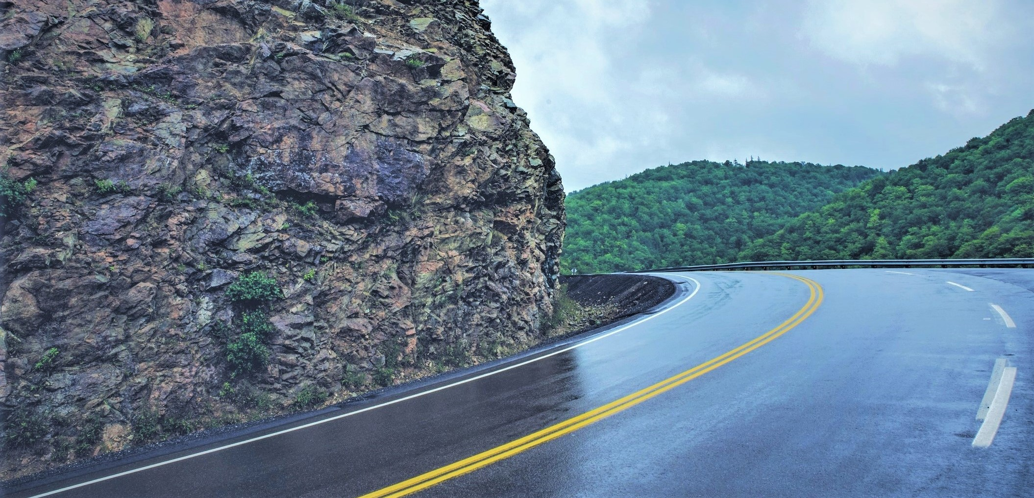 road with sharp curve around a rock formation