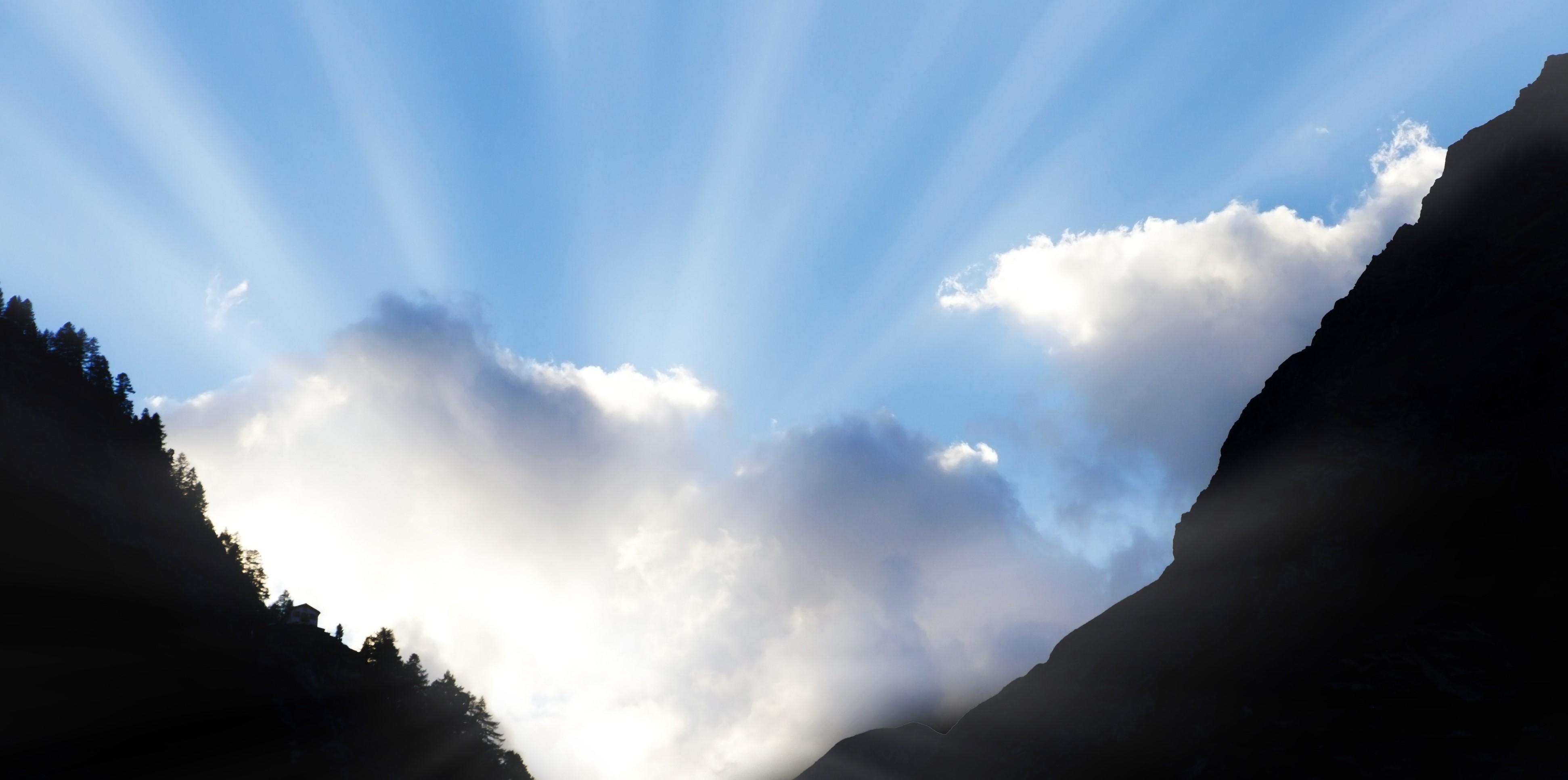 sun shining through clouds between two mountains