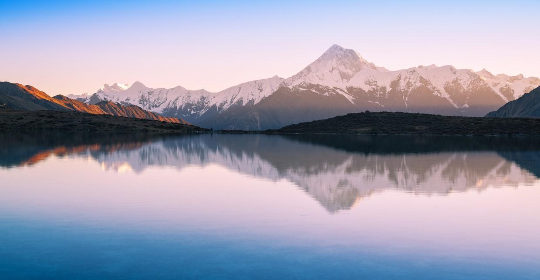 mountains reflecting on a lake during sunrise